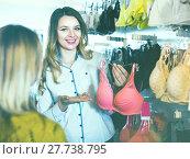 Купить «Female seller demonstrating client bras in underwear store», фото № 27738795, снято 20 марта 2017 г. (c) Яков Филимонов / Фотобанк Лори