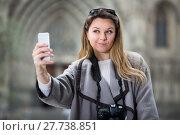 Купить «Cheerful girl taking picture with her phone», фото № 27738851, снято 27 марта 2017 г. (c) Яков Филимонов / Фотобанк Лори