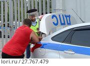 Купить «Инспектор дорожно-патрульной службы полиции оформляет протокол о нарушении правил дорожного движения», фото № 27767479, снято 3 августа 2017 г. (c) Free Wind / Фотобанк Лори