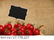 Купить «Red tomatoes in box with price sign over canvas», фото № 27778227, снято 20 июля 2019 г. (c) PantherMedia / Фотобанк Лори