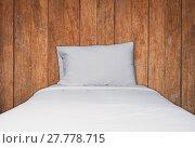 Купить «Close up white bedding and pillow on wooden texture background», фото № 27778715, снято 20 февраля 2019 г. (c) PantherMedia / Фотобанк Лори