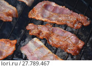 Купить «Crispy smoked bacon slices cooked on bbq grill», фото № 27789467, снято 17 июля 2019 г. (c) PantherMedia / Фотобанк Лори