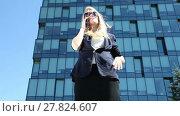 Купить «Business woman talking on cell phone on the background of office building», видеоролик № 27824607, снято 9 июля 2015 г. (c) Алексей Кузнецов / Фотобанк Лори