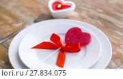 Купить «close up of red heart shaped lollipop on plate», видеоролик № 27834075, снято 10 февраля 2018 г. (c) Syda Productions / Фотобанк Лори