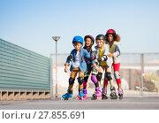 Купить «Happy kids rollerblading in a row outdoors», фото № 27855691, снято 14 октября 2017 г. (c) Сергей Новиков / Фотобанк Лори