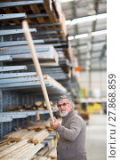 Купить «Man choosing and buying construction wood in a DIY store for his DIY home re-modeling project», фото № 27868859, снято 22 сентября 2018 г. (c) PantherMedia / Фотобанк Лори