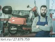 Купить «friendly man worker displaying his workplace in motorcycle workshop», фото № 27879759, снято 23 февраля 2018 г. (c) Яков Филимонов / Фотобанк Лори