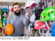 Купить «cheerful male customer examining helmets in sports equipment store», фото № 27880027, снято 24 февраля 2017 г. (c) Яков Филимонов / Фотобанк Лори