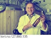 Купить «Adult brewer is standing with beer bottle», фото № 27880135, снято 18 сентября 2017 г. (c) Яков Филимонов / Фотобанк Лори