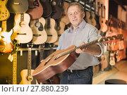 Купить «Male musician buying new acoustic guitar», фото № 27880239, снято 18 сентября 2017 г. (c) Яков Филимонов / Фотобанк Лори