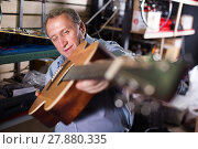 Купить «master is repairing acoustic guitar», фото № 27880335, снято 18 сентября 2017 г. (c) Яков Филимонов / Фотобанк Лори