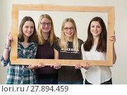 Купить «teenage quartet smiling by wooden frame», фото № 27894459, снято 24 июня 2018 г. (c) PantherMedia / Фотобанк Лори