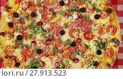 Купить «Rotating pizza with cheese, tomatoes and olives on the red tablecloth close-up», видеоролик № 27913523, снято 13 марта 2016 г. (c) Алексей Кузнецов / Фотобанк Лори