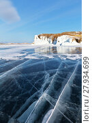 Купить «Frozen Baikal Lake in winter sunny afternoon. A beautiful landscape with smooth blue ice with cracks near the coastal icy rocks of Olkhon Island», фото № 27934699, снято 11 февраля 2018 г. (c) Виктория Катьянова / Фотобанк Лори