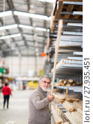 Купить «Man choosing and buying construction wood in a DIY store for his DIY home re-modeling project», фото № 27935451, снято 22 сентября 2018 г. (c) PantherMedia / Фотобанк Лори