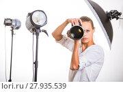 Купить «Pretty, female photographer with digital camera - DSLR and a huge telephoto lens (color toned image; shallow DOF)», фото № 27935539, снято 19 июля 2018 г. (c) PantherMedia / Фотобанк Лори