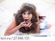 Купить «Upset Woman in Tiara Drinking Wine and Cramming Chocolates in Bedroom», фото № 27940131, снято 20 марта 2018 г. (c) PantherMedia / Фотобанк Лори