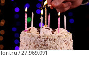 One's hand lit a candles of the birthday cake in front of black background close-up. Стоковое видео, видеограф Алексей Кузнецов / Фотобанк Лори