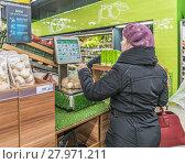 """Купить «Супермаркет """"Перекресток"""". Овощной отдел. Покупательница взвешивает лук на электронных весах», эксклюзивное фото № 27971211, снято 11 июля 2016 г. (c) Виктор Тараканов / Фотобанк Лори"""