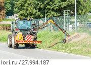 Купить «Tractor mowing green grass along the side of the road», фото № 27994187, снято 22 января 2019 г. (c) PantherMedia / Фотобанк Лори