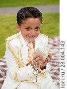 Купить «Young First Communion boy smiling with prayer book and rosary», фото № 28004143, снято 21 марта 2018 г. (c) PantherMedia / Фотобанк Лори