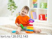 Купить «toddler boy playing indoors with developmental toy sitting on soft carpet», фото № 28012143, снято 20 марта 2018 г. (c) Оксана Кузьмина / Фотобанк Лори