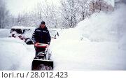 Купить «The janitor clears the track with a snowplow in the courtyard of an apartment building», видеоролик № 28012423, снято 7 февраля 2018 г. (c) Aleksandr Lutcenko / Фотобанк Лори