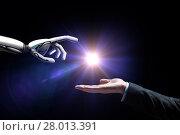 Купить «robot and human hand flash light over black», фото № 28013391, снято 6 сентября 2016 г. (c) Syda Productions / Фотобанк Лори