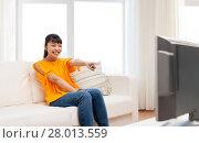 Купить «happy asian woman with watching tv at home», фото № 28013559, снято 9 марта 2016 г. (c) Syda Productions / Фотобанк Лори