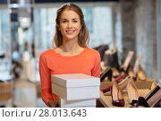 Купить «woman or shop assistant with shoe boxes at store», фото № 28013643, снято 22 сентября 2017 г. (c) Syda Productions / Фотобанк Лори