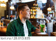 Купить «man drinking green beer at bar or pub», фото № 28013835, снято 22 апреля 2015 г. (c) Syda Productions / Фотобанк Лори