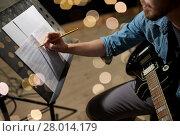 Купить «man with guitar writing to music book at studio», фото № 28014179, снято 18 августа 2016 г. (c) Syda Productions / Фотобанк Лори