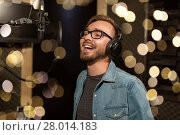 Купить «man with headphones singing at recording studio», фото № 28014183, снято 18 августа 2016 г. (c) Syda Productions / Фотобанк Лори