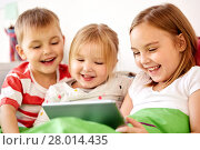 Купить «happy little kids with tablet pc in bed at home», фото № 28014435, снято 15 октября 2017 г. (c) Syda Productions / Фотобанк Лори