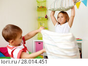 Купить «kids playing and fighting by pillows at home», фото № 28014451, снято 15 октября 2017 г. (c) Syda Productions / Фотобанк Лори