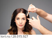 Купить «styling hair woman in a hair salon. curls,hair full of volume.\nportrait of a beautiful woman on a black background.», фото № 28015927, снято 16 октября 2019 г. (c) PantherMedia / Фотобанк Лори