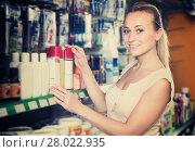 cheerful young woman customer choosing paint medium in bottle in hypermarket. Стоковое фото, фотограф Яков Филимонов / Фотобанк Лори