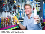 Купить «Positive man customer picking sealing component», фото № 28022939, снято 22 мая 2019 г. (c) Яков Филимонов / Фотобанк Лори