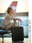 Купить «Young female passenger at the airport, waiting for her flight boarding call (color toned image; shallow DOF)», фото № 28041311, снято 30 марта 2020 г. (c) PantherMedia / Фотобанк Лори