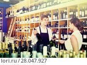 Купить «portrait of male seller showing bottle of wine to female customer in wine shop», фото № 28047927, снято 20 мая 2019 г. (c) Яков Филимонов / Фотобанк Лори