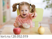 Купить «cute child girl eating breakfast at kindergarten.», фото № 28052019, снято 7 декабря 2019 г. (c) Оксана Кузьмина / Фотобанк Лори