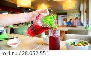 Купить «Teen pours fruit mint lemonade into glass in cafe», видеоролик № 28052551, снято 24 июля 2017 г. (c) Володина Ольга / Фотобанк Лори