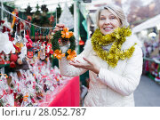 Купить «Woman is preparing for Christmas and choosing wreath for her house», фото № 28052787, снято 21 декабря 2017 г. (c) Яков Филимонов / Фотобанк Лори