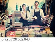 Купить «Two workers selling cheese and sausages», фото № 28052843, снято 22 июля 2018 г. (c) Яков Филимонов / Фотобанк Лори