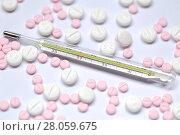 Купить «Рассыпанные таблетки и градусник на белом фоне», фото № 28059675, снято 2 января 2018 г. (c) Роман Рожков / Фотобанк Лори