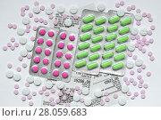 Купить «Таблетки в блистерной упаковке и россыпью на фоне аптечных чеков», фото № 28059683, снято 2 января 2018 г. (c) Роман Рожков / Фотобанк Лори