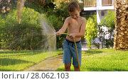 Купить «Child watering lawn with hose», видеоролик № 28062103, снято 18 июля 2019 г. (c) Данил Руденко / Фотобанк Лори