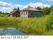 Купить «Старый деревянный разрушающийся дом у пруда», фото № 28063267, снято 10 августа 2017 г. (c) Pukhov K / Фотобанк Лори