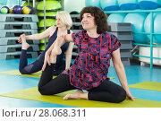 Купить «Women doing yoga exercise in the gym», фото № 28068311, снято 18 февраля 2018 г. (c) Владимир Мельников / Фотобанк Лори