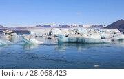 Купить «Amazing view of floating icebergs in the glacial lake Jokulsarlon on the background of clear blue sky, Iceland», видеоролик № 28068423, снято 6 октября 2017 г. (c) Алексей Кузнецов / Фотобанк Лори